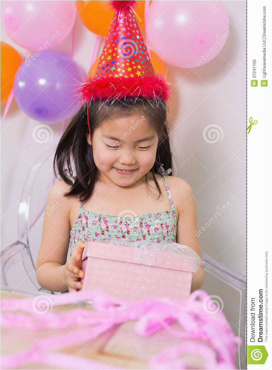 little girl with gift box at her birthday party stock
